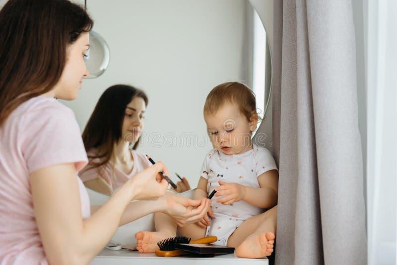 Macierzysta i dziecko jej dziewczyna robi makeup i mie? zabaw? blisko odzwierciedla zdjęcie royalty free