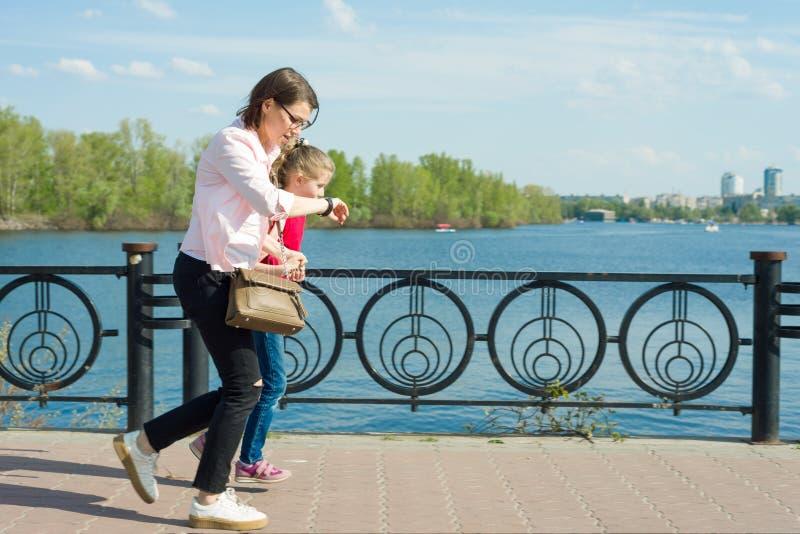 Macierzysta i mała córka iść szkoła Kobiet spojrzenia przy jej zegarkiem, pośpiechy, są opóźneni, szybko iść zdjęcia stock