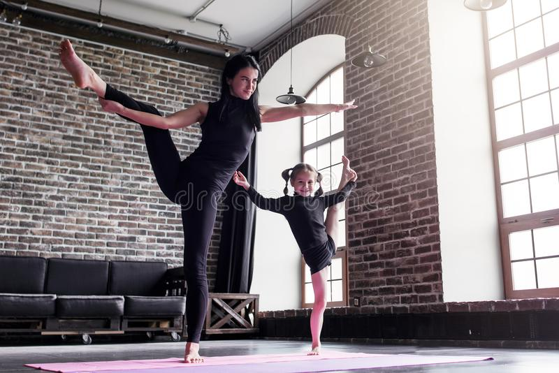 Macierzysta i mała córka robi stojący rozszczepionego nogi rozciągania ćwiczenie utrzymuje równowagę obraz royalty free