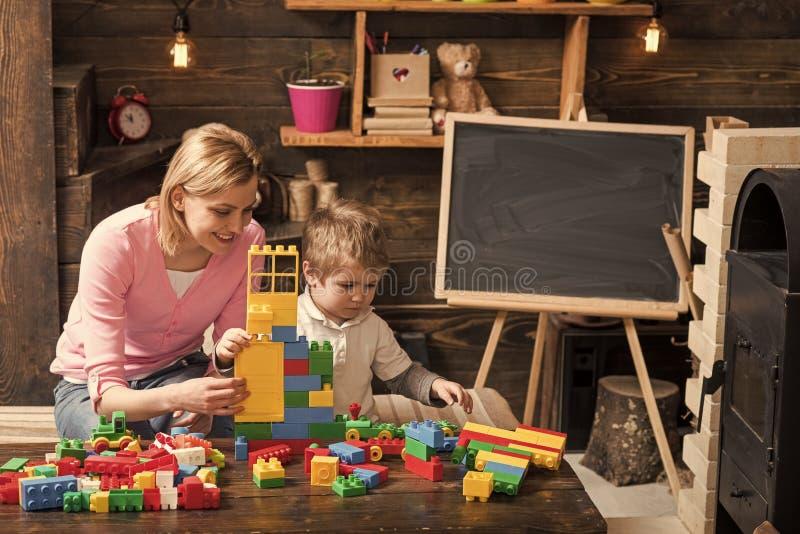 Macierzysta i szczęśliwa syn sztuka z konstruktorem Macierzyństwa pojęcie Pepiniera z zabawkami i chalkboard na tle, kopia obraz stock