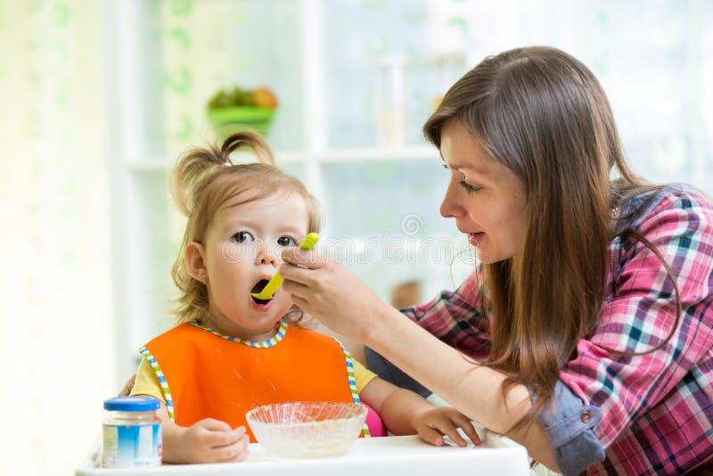 Macierzysta karmienie dzieciaka dziewczyna przy kuchnią zdjęcia stock