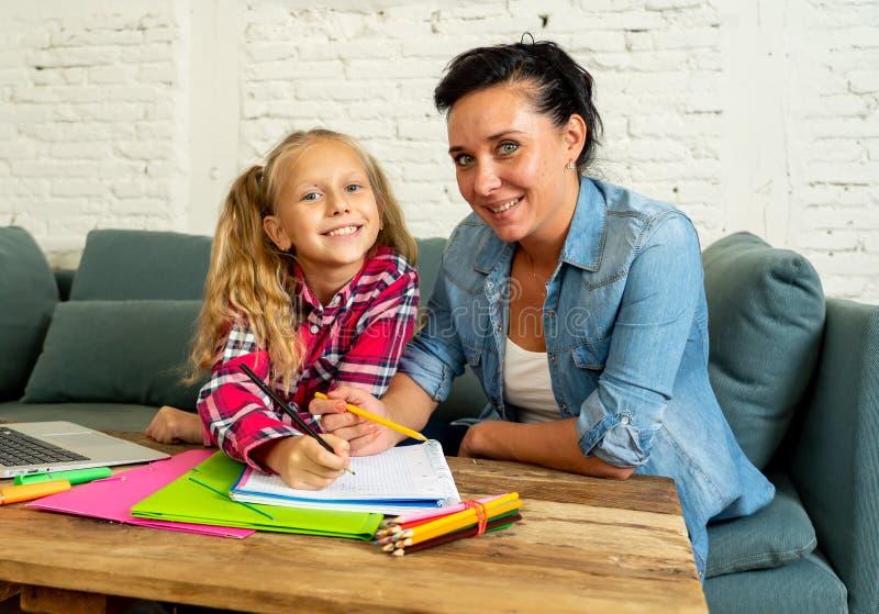 Macierzysta pomaga młoda dziewczyna robi pracie domowej z laptopem i szkolnymi książkami siedzi na kanapie w wychowywać pracę dom fotografia royalty free