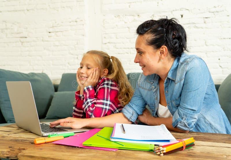 Macierzysta pomaga młoda dziewczyna robi pracie domowej z laptopem i szkolnymi książkami siedzi na kanapie w wychowywać pracę dom zdjęcia stock