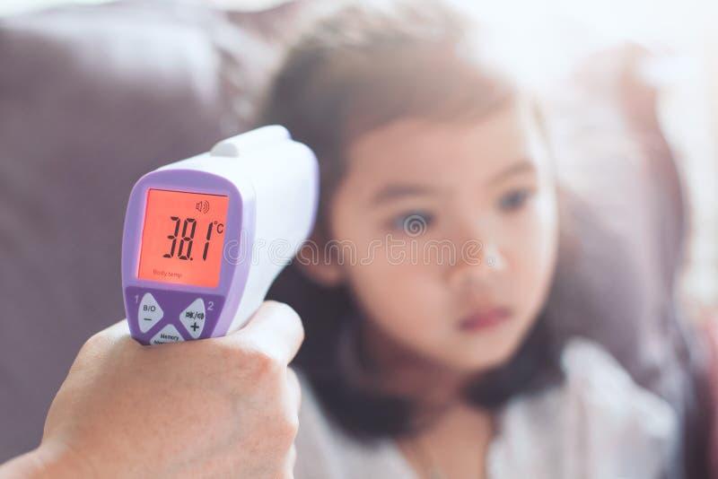 Macierzysta pomiarowa temperatura jej chora azjatykcia małe dziecko dziewczyna obrazy stock