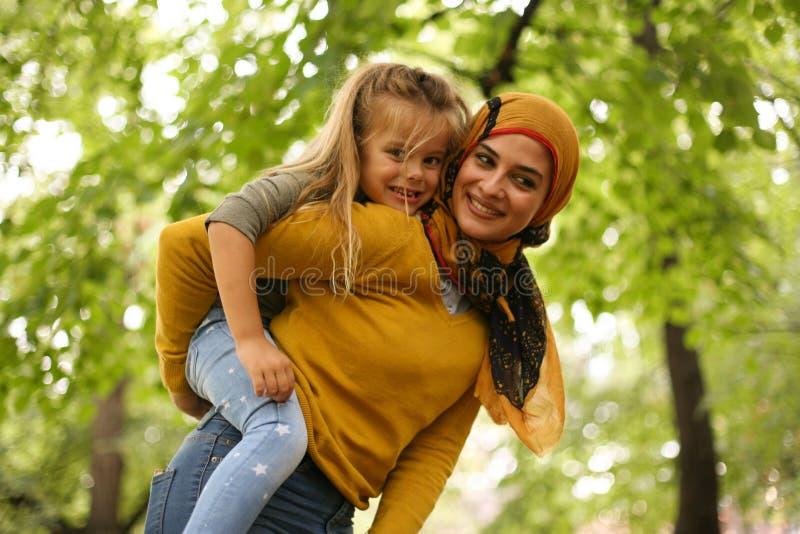Macierzysta przewożenie córka dalej piggyback muslim zdjęcie stock