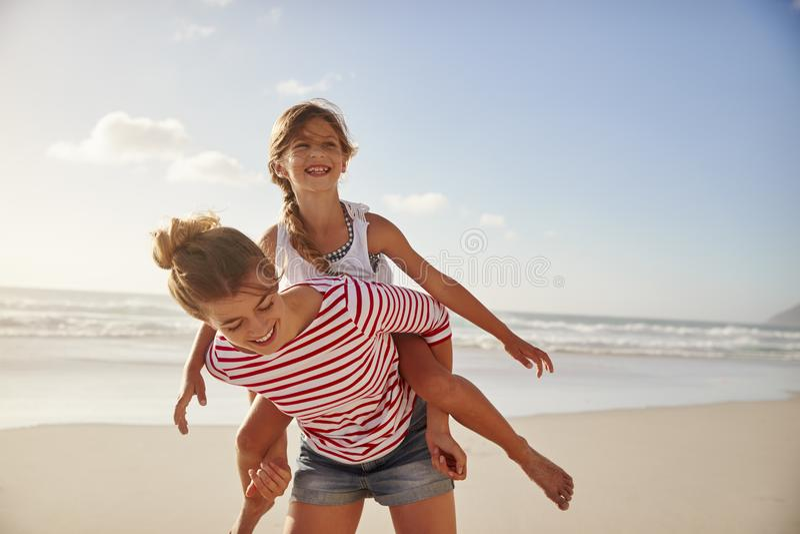 Macierzysta przewożenie córka Na ramionach Na plaża wakacje fotografia stock