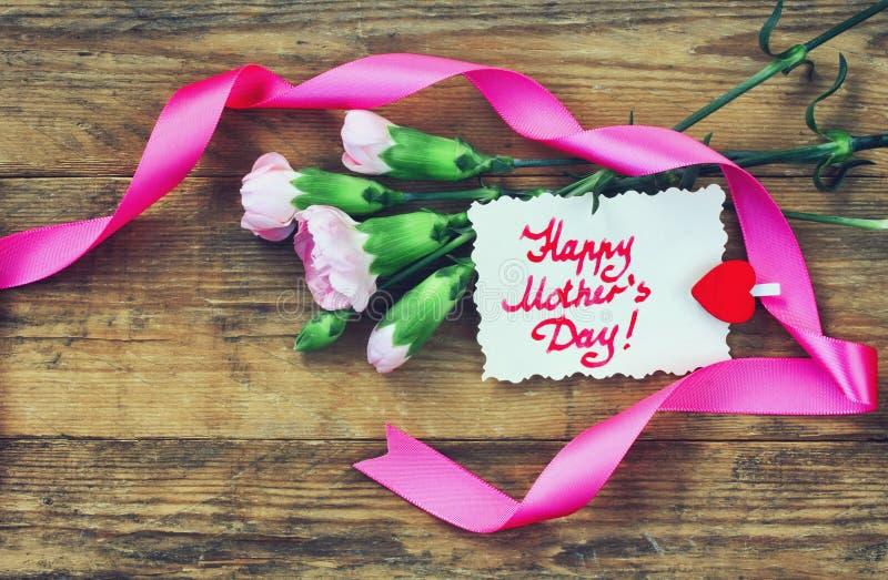 Macierzysta ` s dnia pocztówka, różowi goździki i notatka, zdjęcie stock