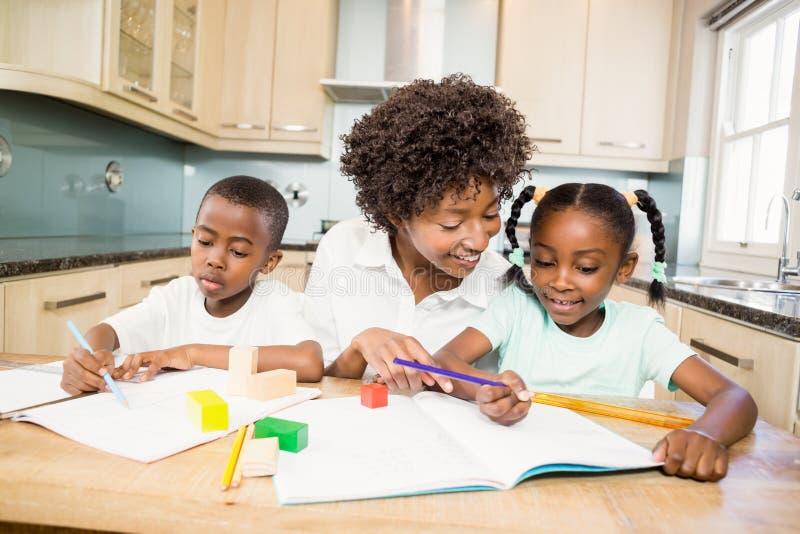 Macierzysta sprawdza dziecko praca domowa obrazy stock