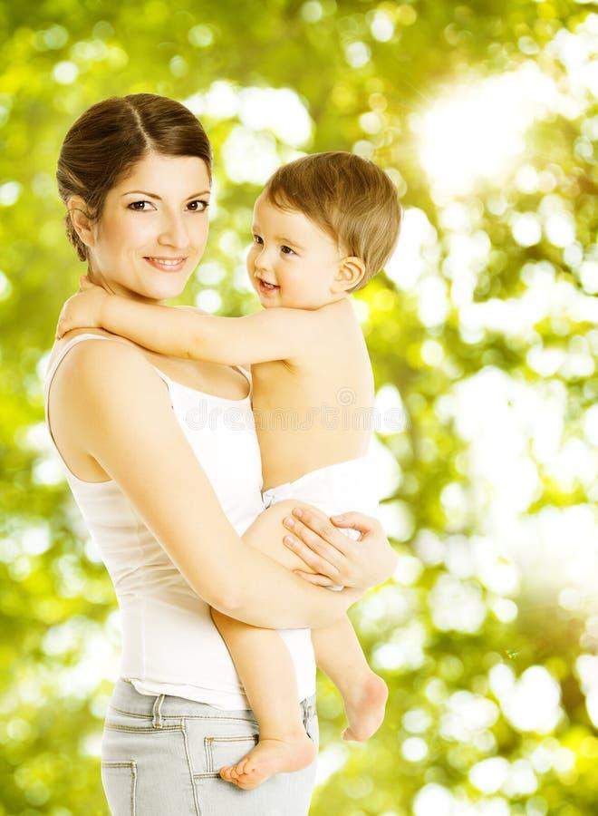 Macierzystego dziecka szczęśliwy ono uśmiecha się Dziecko w pieluszki obejmowania mama nad g obrazy stock
