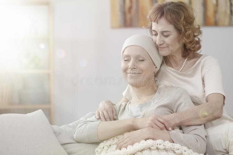 Macierzystego przytulenia szczęśliwa chora kobieta zdjęcie stock