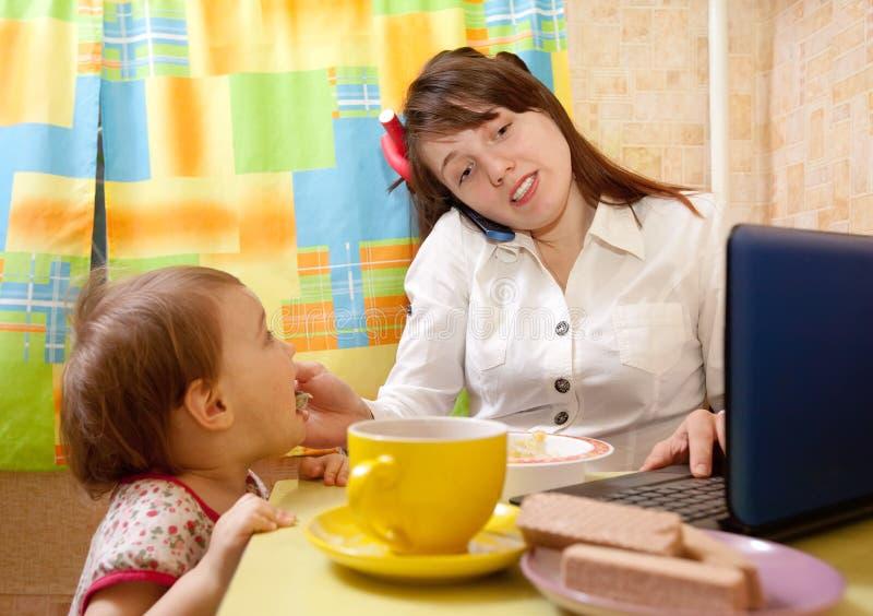 Macierzysty żywieniowy dziecka i używać latop obraz royalty free