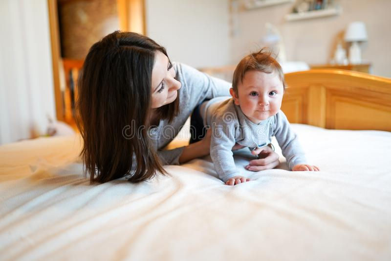 macierzysty bawi? si? z jej dzieckiem w sypialni szcz??liwa rodzina fotografia stock
