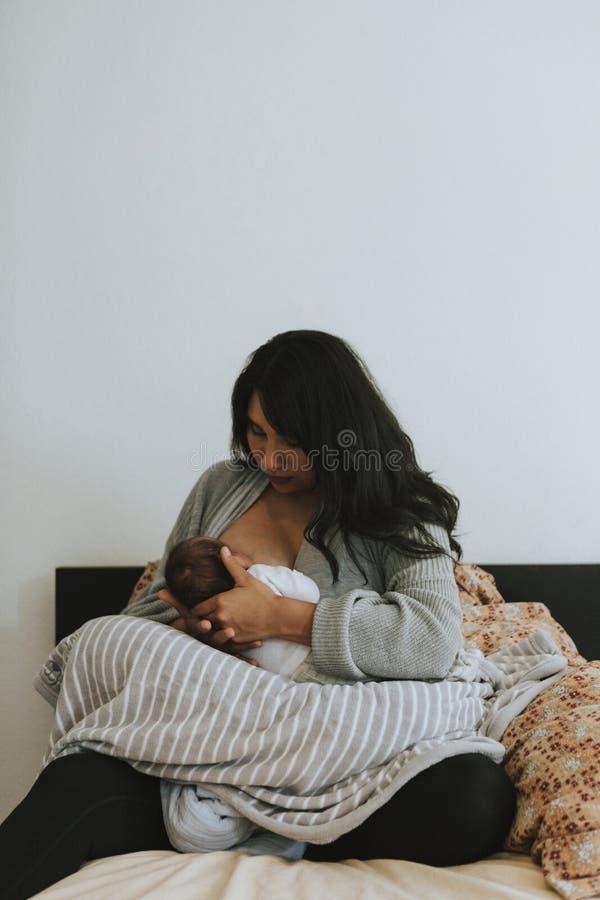 Macierzysty breastfeeding jej dziecka w domu fotografia royalty free