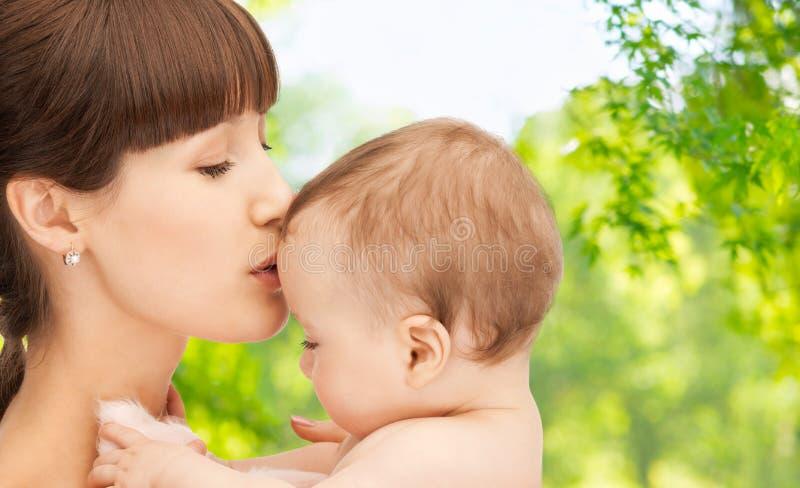 Macierzysty całowania dziecko nad zielonym naturalnym tłem fotografia royalty free