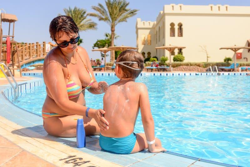 Macierzysty chronienie jej syn z sunscreen obrazy stock