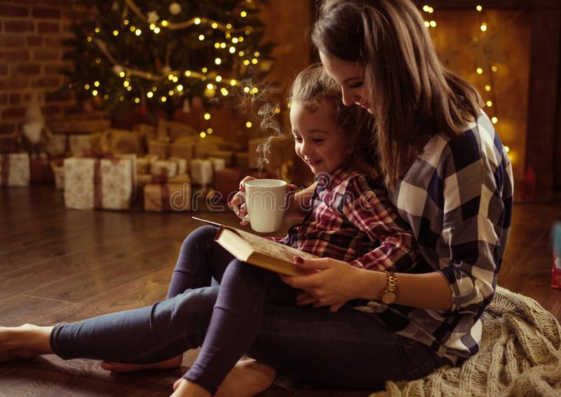 Macierzysty czytanie książka dla jej córki w spokoju, zima eveneing zdjęcie royalty free