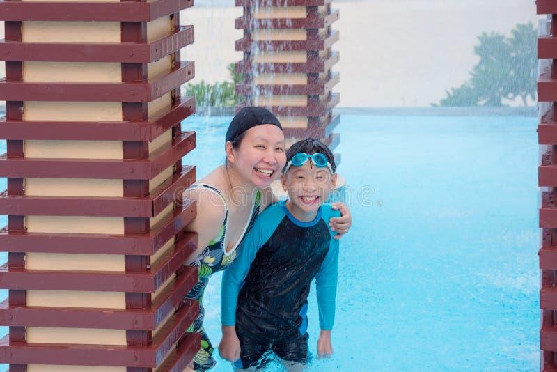 Macierzysty i jej synu ono uśmiecha się w pływackim basenie obrazy stock