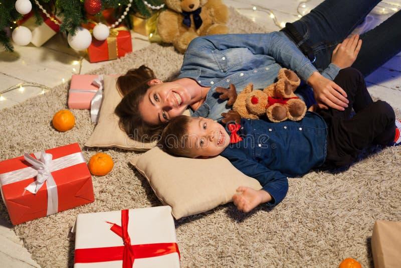 Macierzysty i młody syn jest z tyłu choinki z prezentami fotografia royalty free