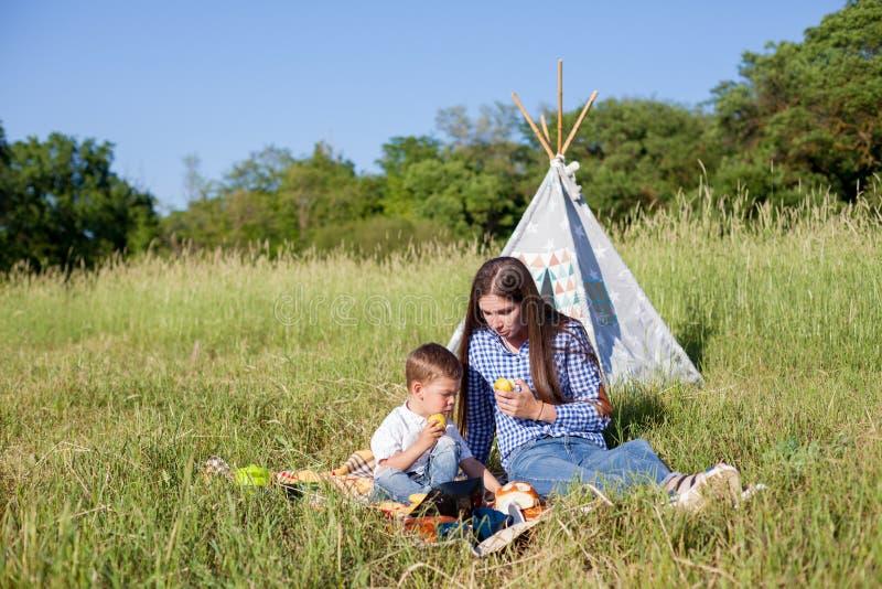 Macierzysty i młody syna łasowanie przy pinkinu outdoors namiotem fotografia royalty free