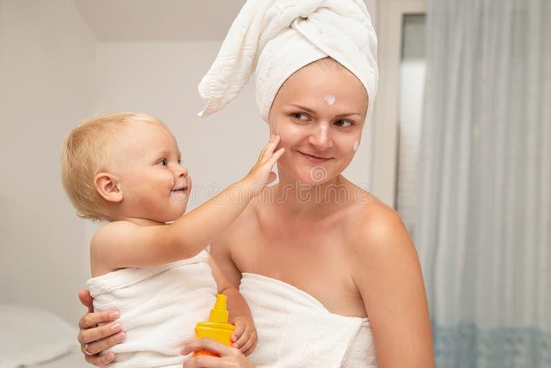 Macierzysty i smiley dziecięcy dziecko w białych ręcznikach po kąpać się stosuje sunscreen po słońce płukanki lub Dziecko skóry o fotografia stock