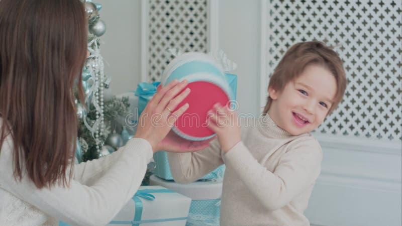 Macierzysty i szczęśliwy syn sprawdza prezenty siedzi blisko choinki fotografia royalty free