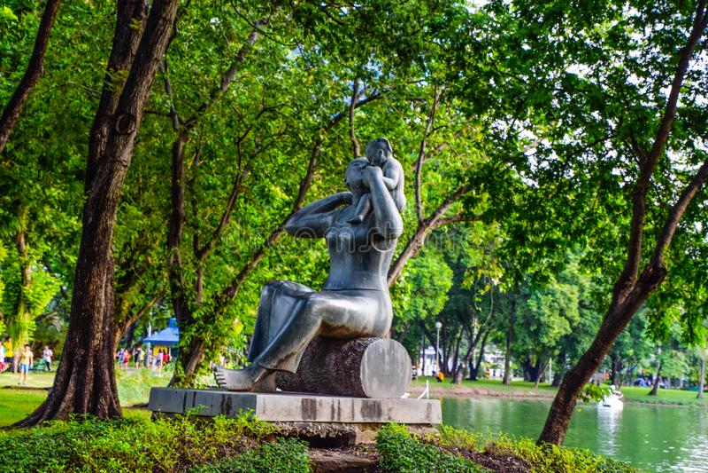 Macierzysty kamienny statuy przewożenia dziecko w parku przy Bangkok, Tajlandia fotografia royalty free