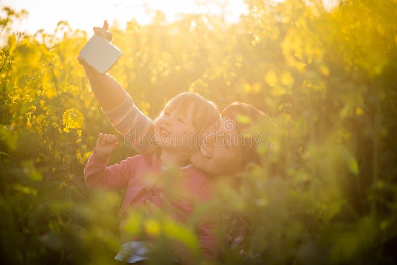 Macierzysty klika selfie z córką na rapeseed polu obraz royalty free