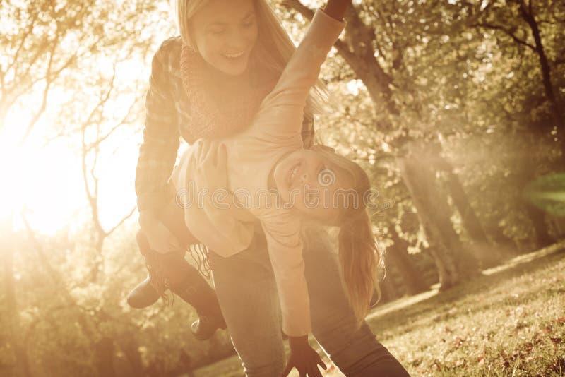 Macierzysty kursowanie z ona w parkowej małej córce i chwycie zdjęcie stock