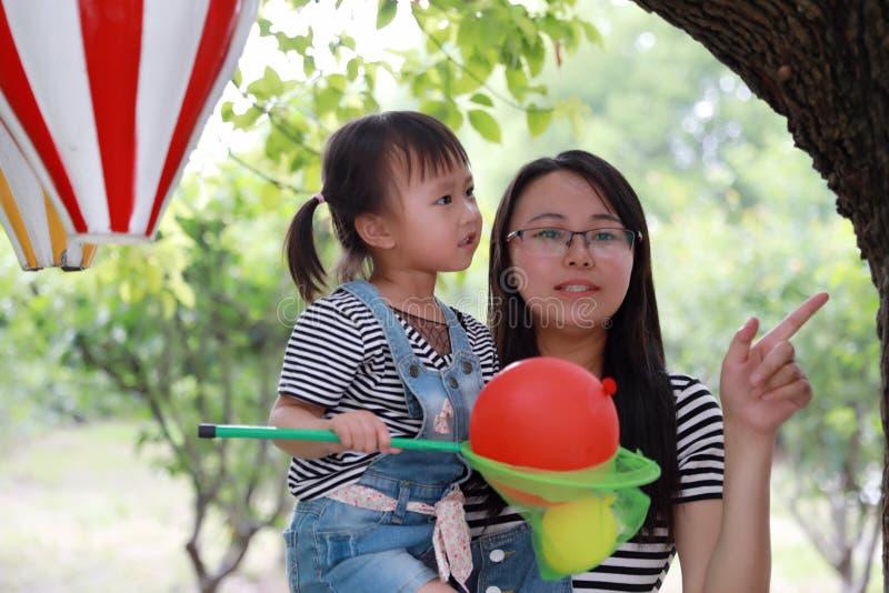 Macierzysty mama uścisk ściska jej córki uśmiechu śmiech zabawę cieszyć się czas wolnego w lato parka dziecka dzieciństwa szczęśl obraz royalty free