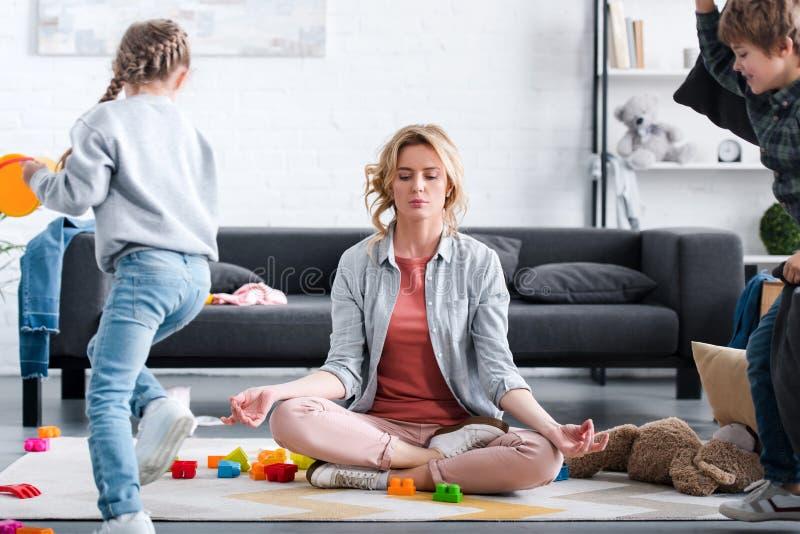 macierzysty medytować w lotosowej pozycji podczas gdy niegrzeczny dzieciaków bawić się royalty ilustracja