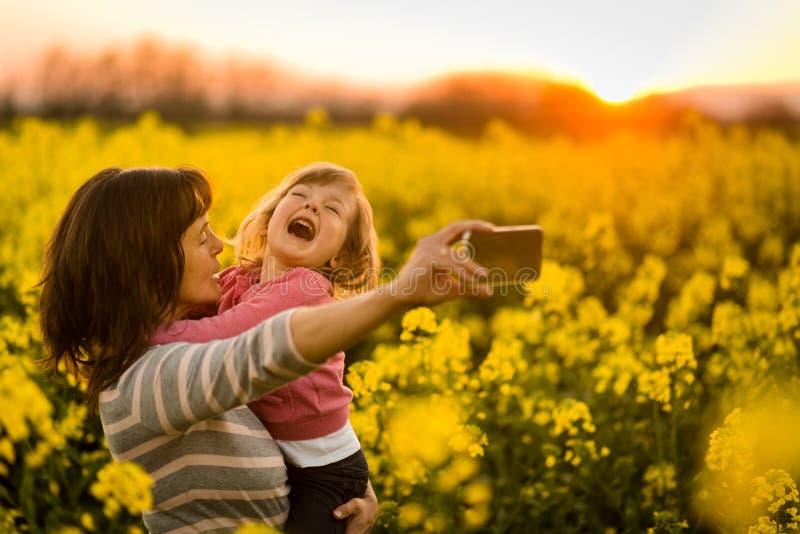 Macierzysty mienie dziewczyny dziecko w rękach, klika selfie obrazy royalty free