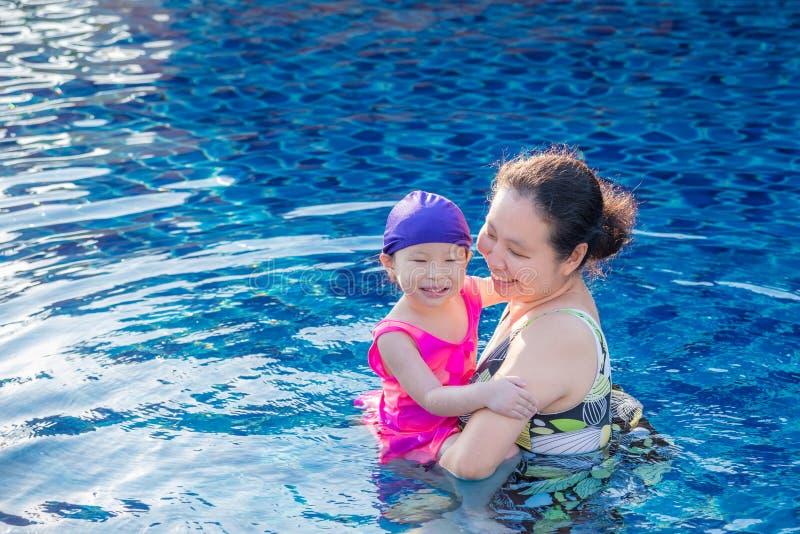 Macierzysty mienie jej córka w basenie zdjęcie royalty free