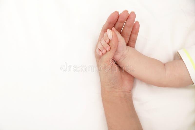 Macierzysty mienie jej dziecka ręka na łóżku, odgórny widok zdjęcie stock
