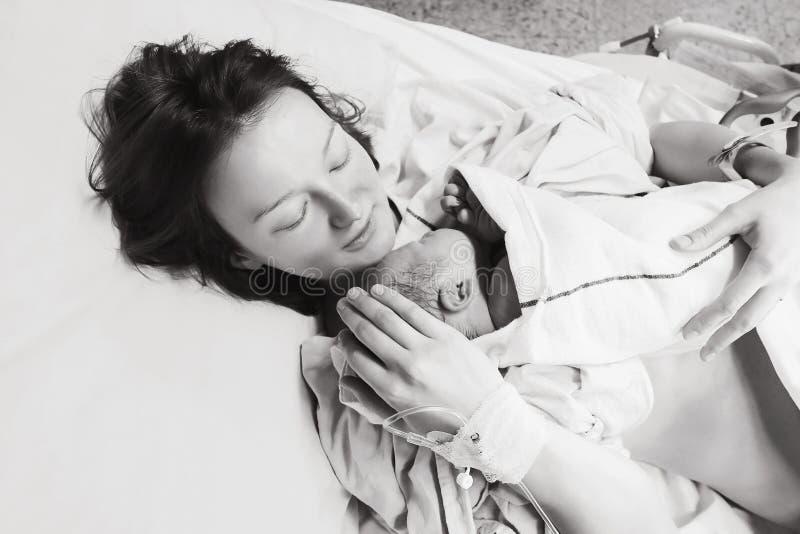 Macierzysty mienie jej nowonarodzony dziecko po pracy w szpitalu obraz royalty free