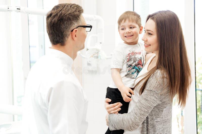 Macierzysty mienie jej syn i opowiadać dentysta w klinice obrazy royalty free