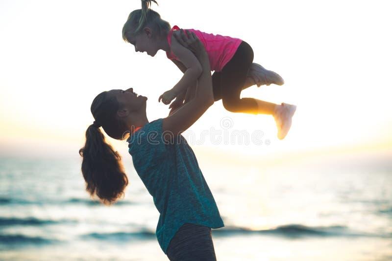 Macierzysty miotania dziecko up w jej powietrzu przy zmierzchem na plaży zdjęcia royalty free