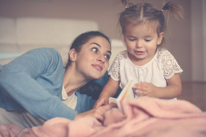 Macierzysty nauczanie jej córka czytelnicza książka w domu fotografia royalty free