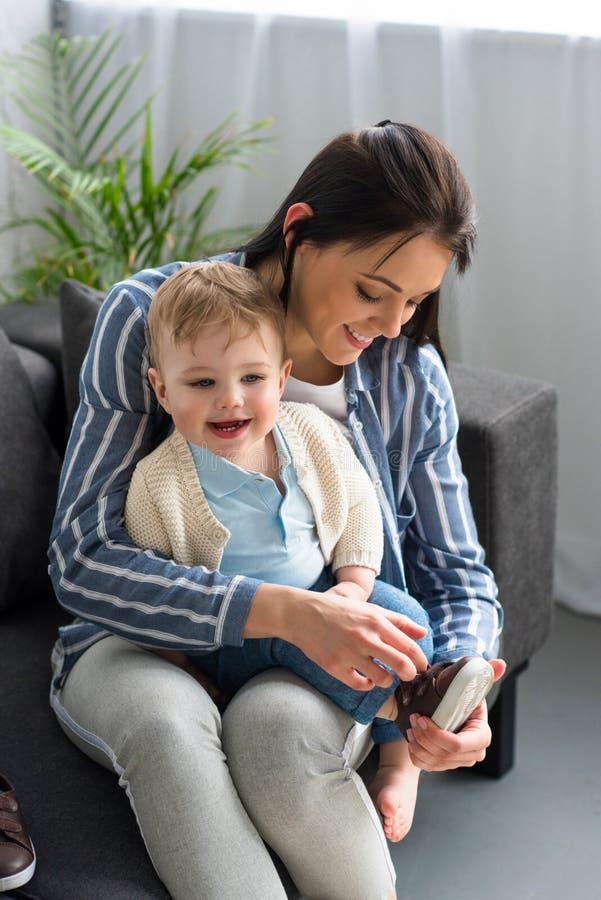 macierzysty opatrunkowy rozochocony mały dziecko na kanapie zdjęcia royalty free