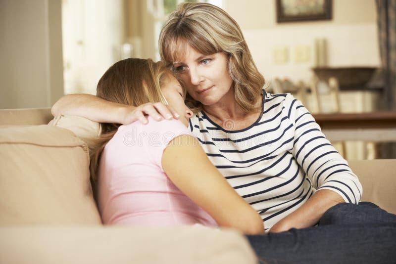 Macierzysty Pociesza Nastoletniej córki obsiadanie Na kanapie W Domu zdjęcie royalty free