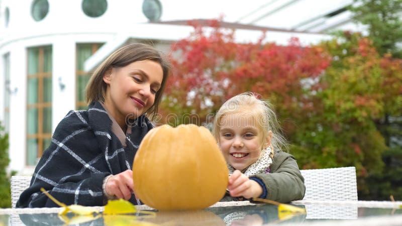 Macierzysty pomaga dziecko rzeźbić dyniowego Jack dla Halloween, jesieni przyjęcie, zabawa obraz stock