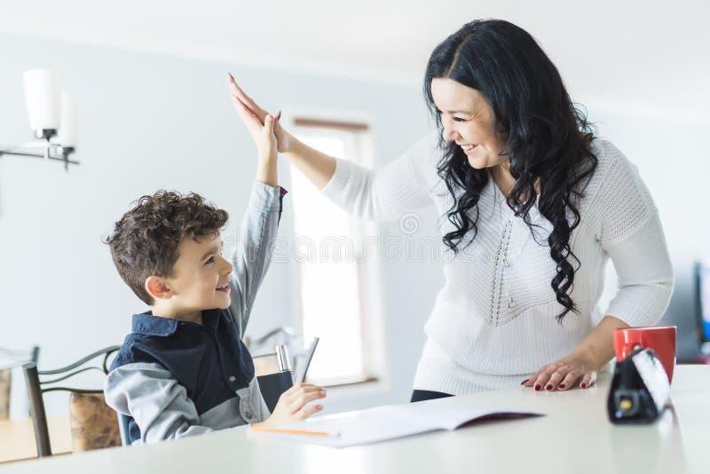 Macierzysty Pomaga syn dla pracy domowej w domu zdjęcia royalty free