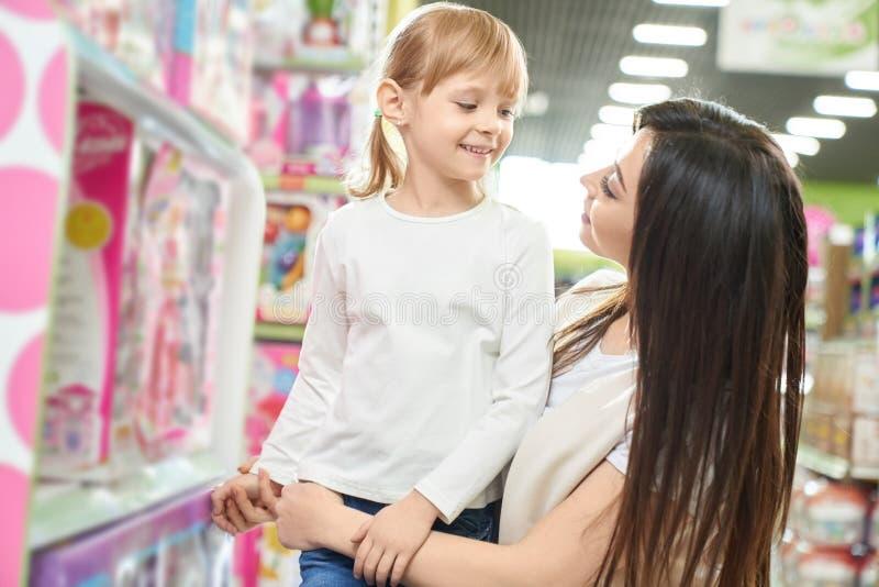 Macierzysty pozowa? z dzieciakiem w zabawkarskim sklepie zdjęcia royalty free