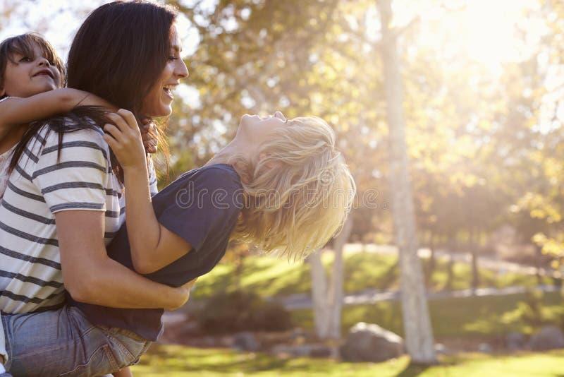 Macierzysty przewożenie syn, córka I Gdy Bawić się W parku obraz royalty free