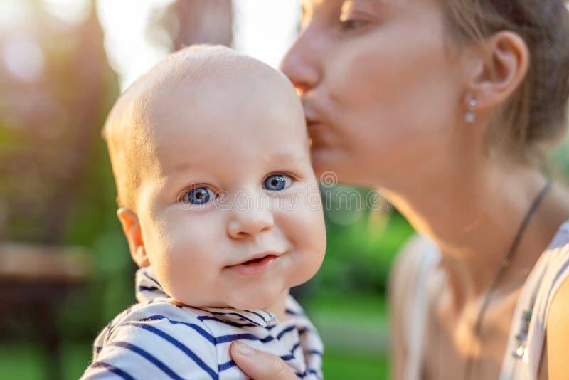 Macierzysty przytulenia i całowania kittle syn outdoors Mama i chłopiec ma zabawę w zielonym owocowego sadu ogródzie wpólnie szcz obrazy royalty free