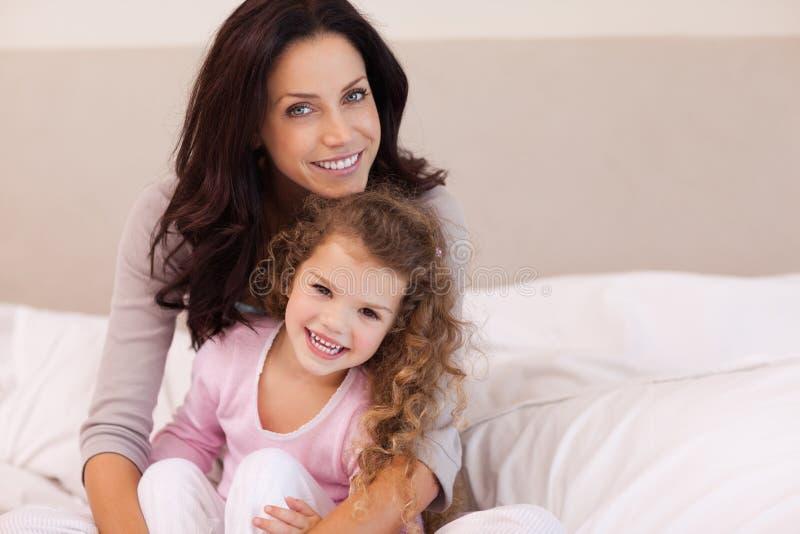 Macierzysty przytulenie jej córka na łóżku zdjęcie royalty free