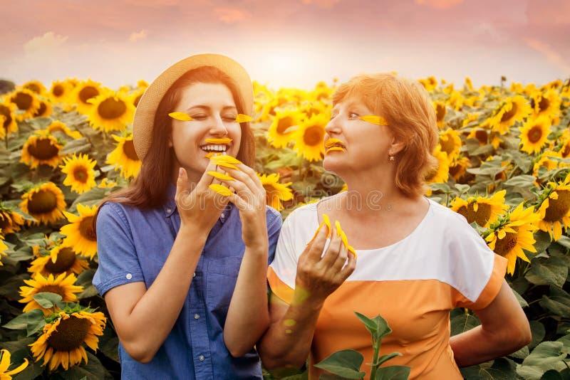 Macierzysty ` s dnia pojęcie Senior macierzysty i jej córka robi z płatków w słonecznika polu manicure'owi i makijażowi zdjęcie stock