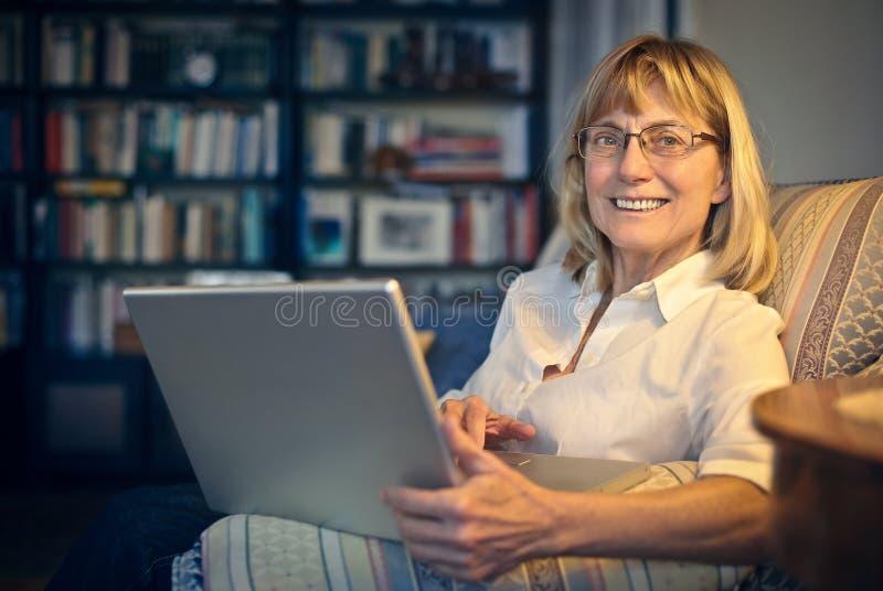 Macierzysty sprawdzać jej komputer obrazy stock