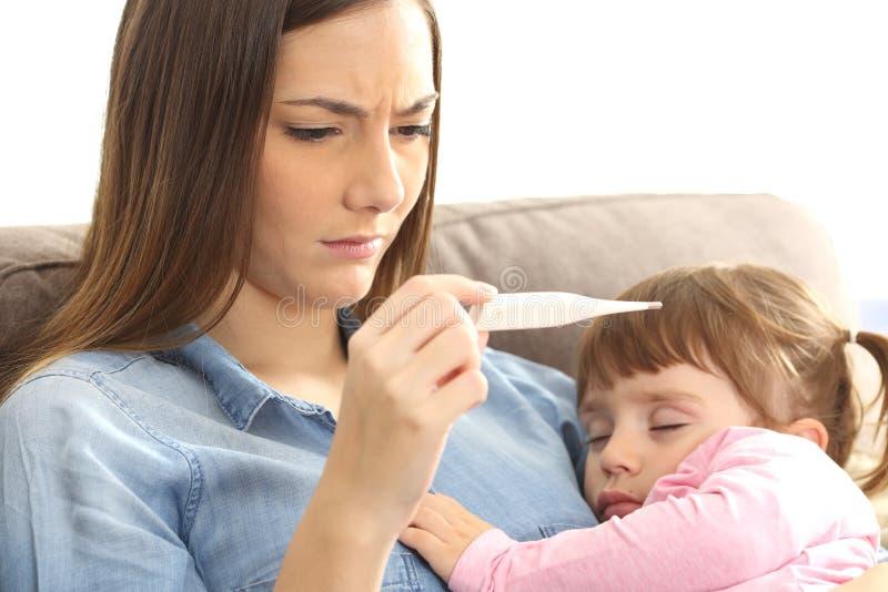 Macierzysty sprawdza termometr z jej chorym dzieckiem zdjęcie stock