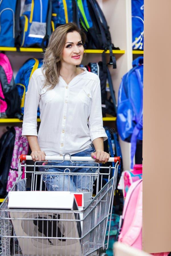 Macierzysty szczęśliwy błękitny biały zakup szkolnej torby centrum handlowego młodej kobiety troley zakupy supermarketa materiały fotografia stock