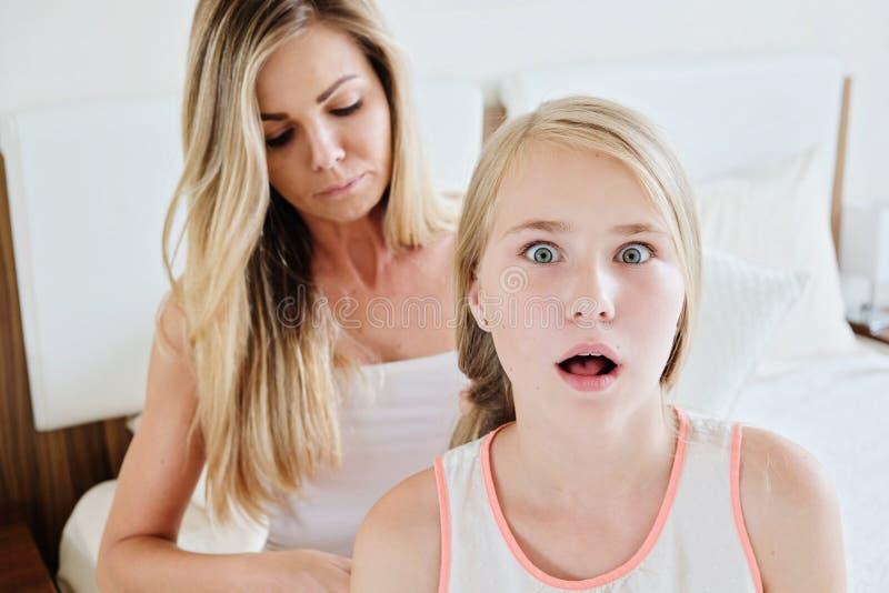 Macierzysty szczotkować długie włosy jej córka w domu obrazy royalty free